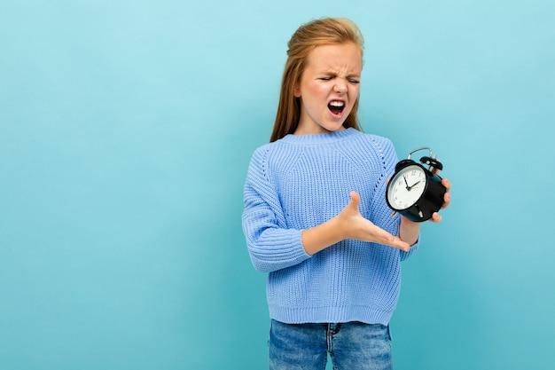 Jolie fille européenne crie et tient un réveil sur un mur bleu clair