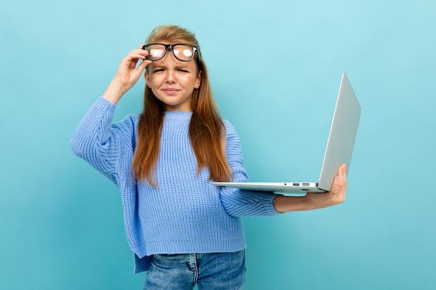 Jolie fille européenne dans des verres avec un ordinateur portable dans les mains sur le mur bleu clair