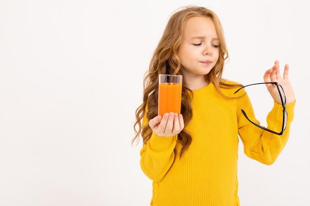 Jolie fille européenne a enlevé ses lunettes et tient un verre de jus de carotte dans sa main