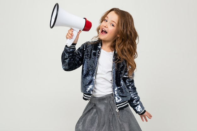 Jolie fille européenne avec un mégaphone rapporte les nouvelles sur un mur blanc pur