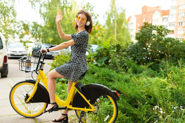 Jolie fille européenne monte un vélo de location dans un parc de la ville