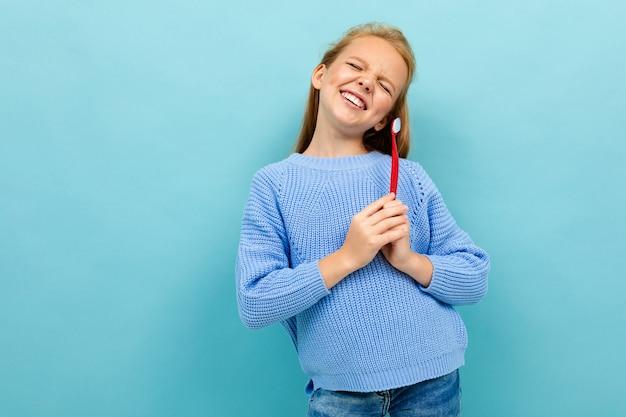 Jolie fille européenne tenant une brosse à dents dans ses mains sur bleu clair
