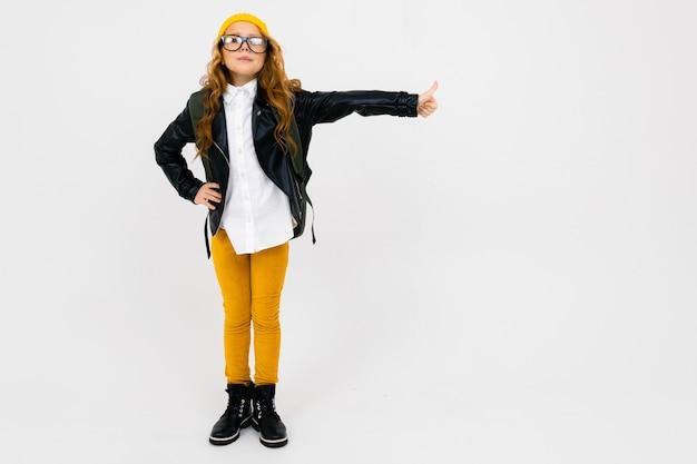 Jolie fille européenne vêtue d'un chapeau jaune, des lunettes et une veste en cuir avec un sac à dos sur le dos en pleine croissance sur blanc