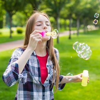 Jolie fille faisant des bulles de savon