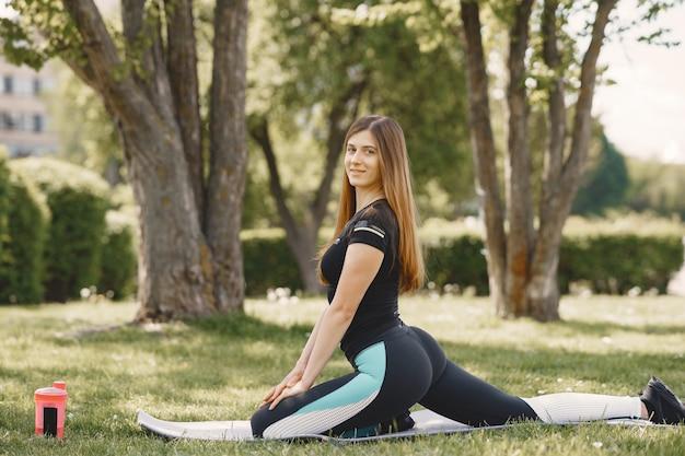 Jolie fille faisant du yoga dans un parc d'été