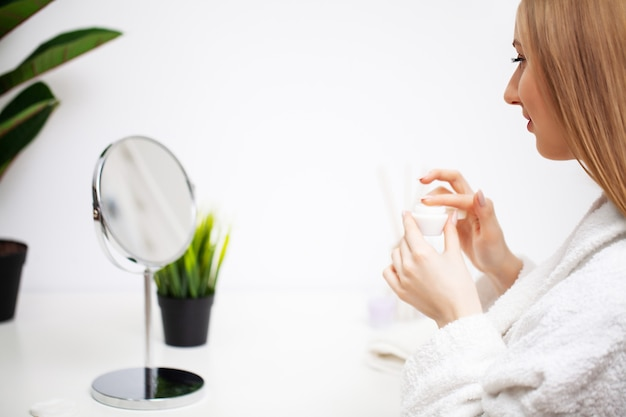 Jolie fille faisant la procédure de soins du visage dans la salle de bain