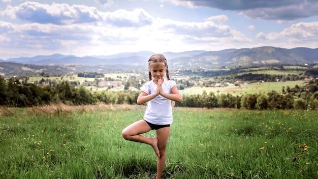 Jolie fille faisant ses exercices du matin au sommet des montagnes dans la nature estivale, exercices du matin, sport et mode de vie sain, à l'extérieur