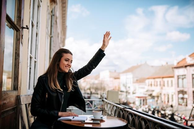 Jolie fille faisant signe à un ami depuis un balcon.