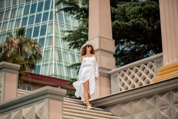 Jolie fille femelle en europe posant. femme frisée en robe de mousseline blanche marchant.