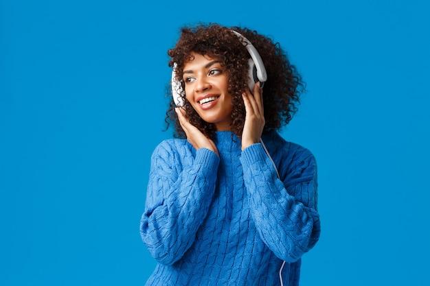 Jolie fille féminine afro-américaine sensuelle avec coupe de cheveux afro, portant un pull d'hiver, regardant à gauche avec un sourire agréable, portant des écouteurs, écoute des chansons.