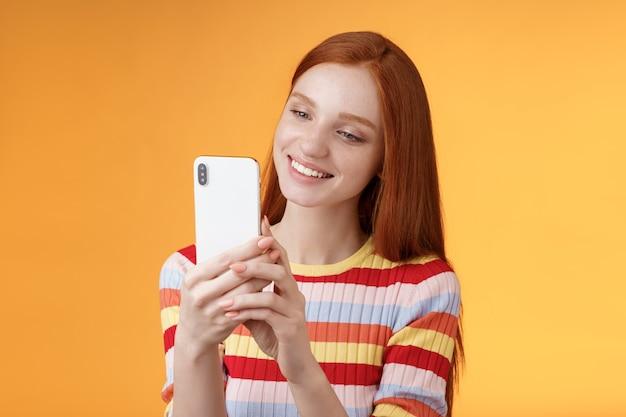 Jolie fille féminine glamour tendre jeune rousse tenant un smartphone prenant des photos d'été vibes urbaines femme blogueuse tir post en ligne histoire debout heureusement fond orange souriant.