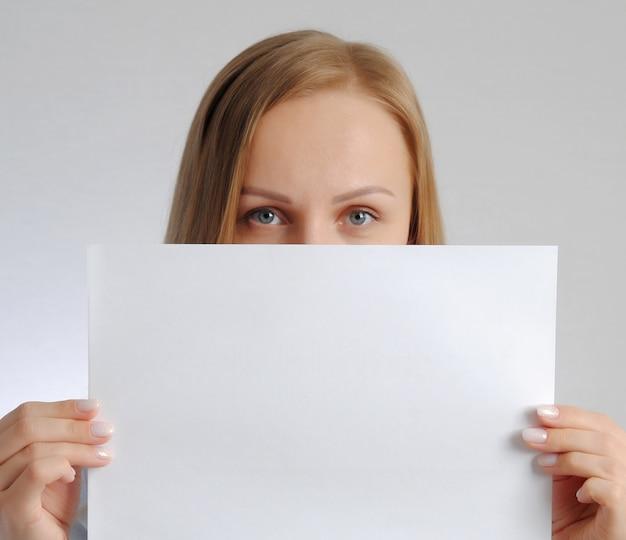 Jolie fille avec une feuille de papier vide