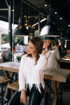 Jolie fille fixant ses cheveux dans un café