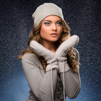 Jolie fille frisée portant des mitaines pendant la neige