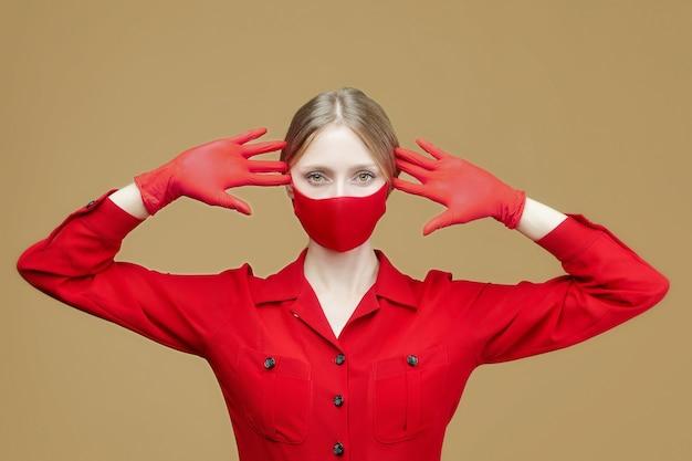 Jolie fille en gants rouges et masque. le concept de prévention du coronavirus covid 19. séance photo en studio sur fond jaune