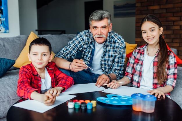 Jolie fille et garçon peinture avec gouache colorée avec leur grand-père.