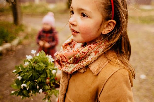 La jolie fille garde un bouquet et se tient dans le parc