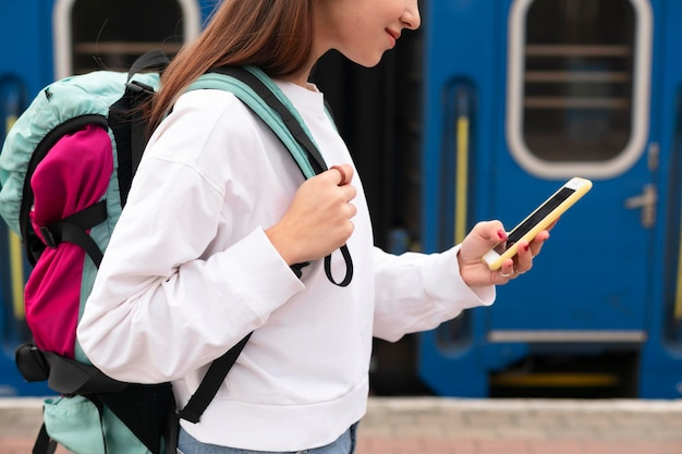 Jolie fille à la gare à l'aide de son smartphone
