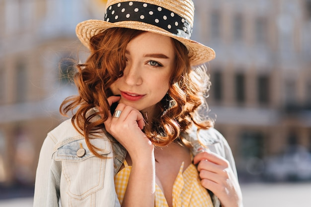 Jolie fille de gingembre aux yeux bleus posant sur la ville floue. photo extérieure d'une superbe jeune femme rousse en veste à la mode.