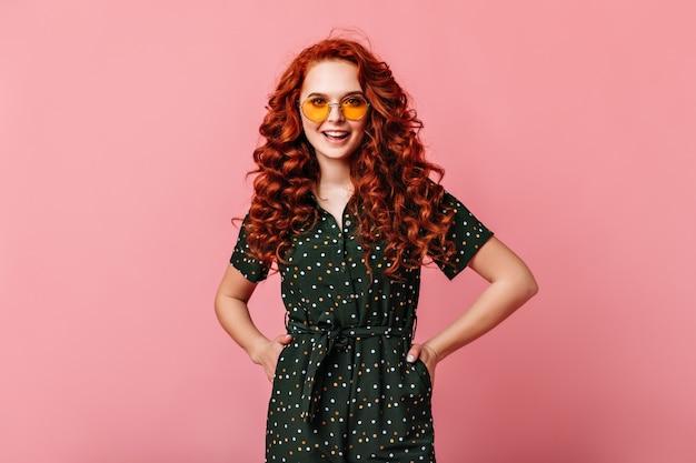 Jolie fille de gingembre debout avec les mains sur les hanches. heureuse jeune femme bouclée à lunettes de soleil posant sur fond rose.