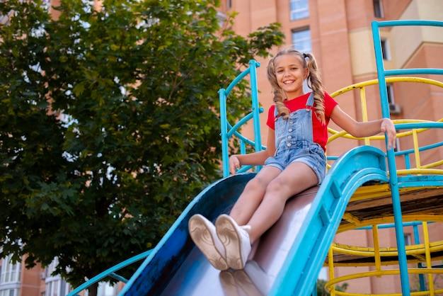 Jolie fille glissant sur un toboggan sur le terrain de jeu