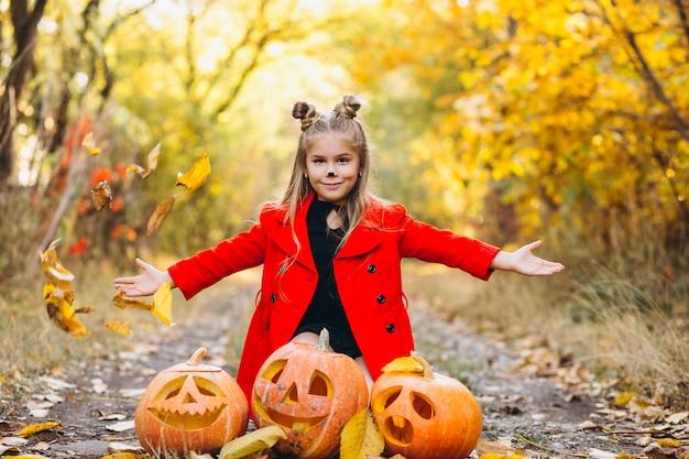 Jolie fille habillée en costume d'halloween à l'extérieur avec des citrouilles