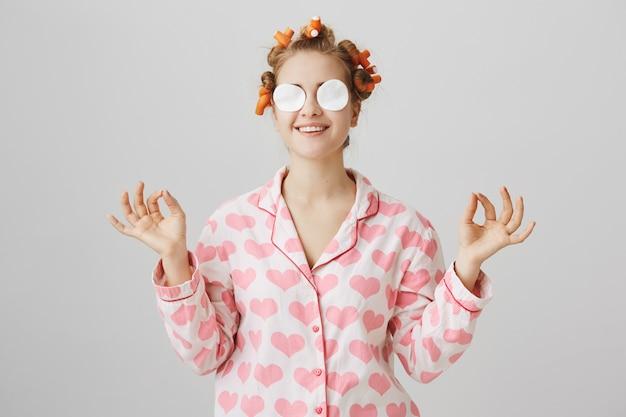 Jolie fille heureuse en vêtements de nuit et bigoudis essuyez le maquillage avec des tampons de coton