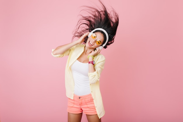 Jolie fille hispanique à la peau bronzée portant un bracelet à la mode et des lunettes orange, écouter de la musique et danser. photo intérieure d'une jolie dame latine en veste de coton jaune s'amusant.