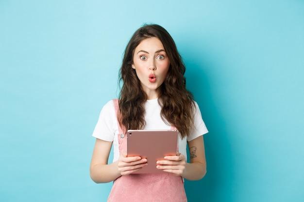 Une jolie fille impressionnée dit wow, regarde excitée devant la caméra, tenant une tablette numérique sur la poitrine, debout dans des vêtements de printemps sur fond bleu
