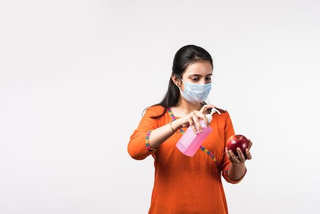 Une jolie fille indienne porte un masque facial désinfectant la pomme ou appliquant un désinfectant sur les fruits