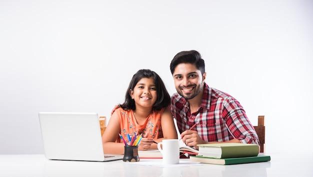 Jolie fille indienne avec son père étudiant ou faisant ses devoirs à la maison à l'aide d'un ordinateur portable et de livres - concept d'enseignement en ligne