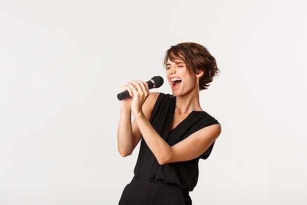 Jolie fille insouciante chantant dans le microphone, effectuant, amusez-vous au karaoké, debout sur blanc.