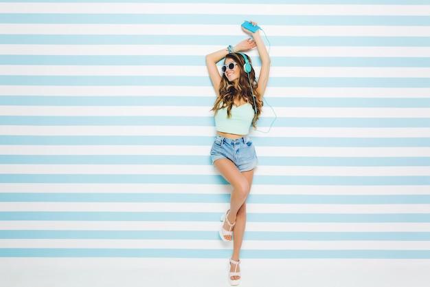 Jolie fille inspirée aux cheveux châtain clair passant du temps à la maison en écoutant de la musique dans des écouteurs. portrait en pied d'une fascinante jeune femme bronzée portant des sandales blanches et un short en jean.