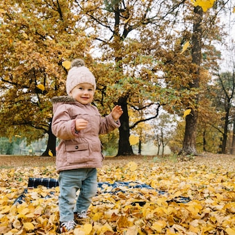 Jolie fille jetant des feuilles dans la forêt d'automne