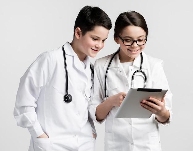 Jolie fille et jeune garçon déguisé en médecin