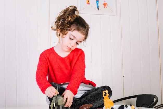 Jolie fille jouant avec des jouets animaux à la maison