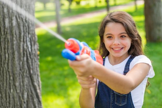 Jolie fille jouant avec un pistolet à eau