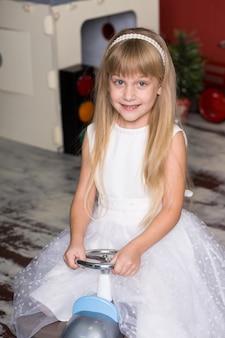 Jolie fille joue avec des petites voitures. conduit un jouet jouet machine à écrire. enfance heureuse