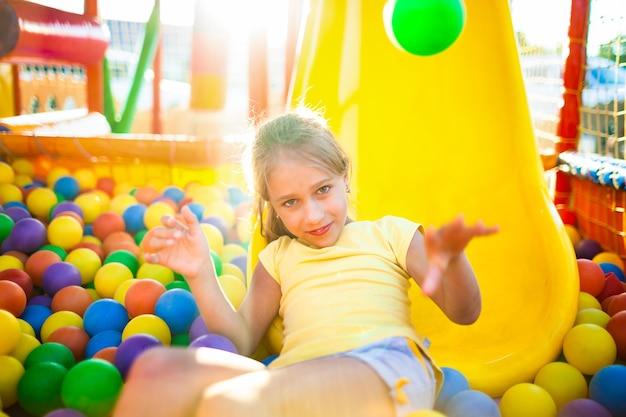 Une jolie fille joyeuse se trouve sur le terrain de jeu avec un équipement doux et lumineux et jette des ballons colorés dans l'appareil photo, profitant du chaud soleil d'été