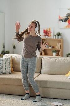 Jolie fille joyeuse en vêtements de sport dansant par la musique dans les écouteurs tout en passant du bon temps à la maison le week-end