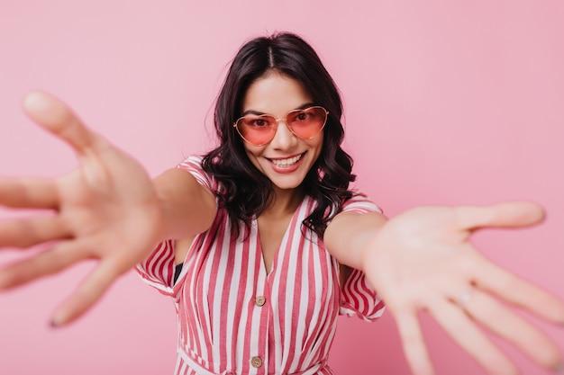 Jolie fille latine dans des verres à la mode posant avec plaisir et rire. plan intérieur d'une femme fascinante en tenue rose rayée.
