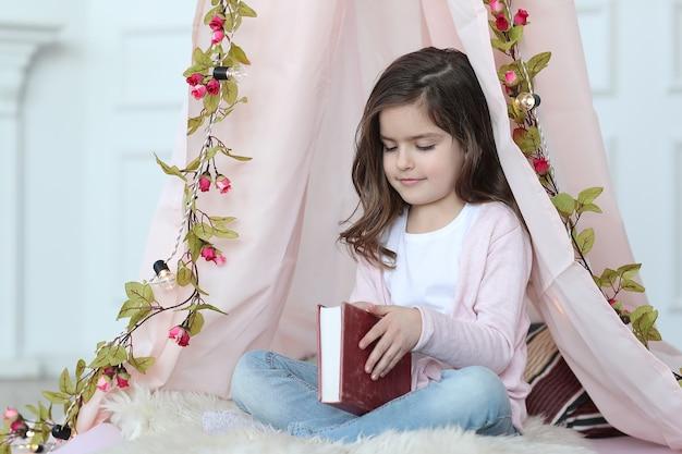 Jolie fille lisant un livre autour de la décoration mignonne