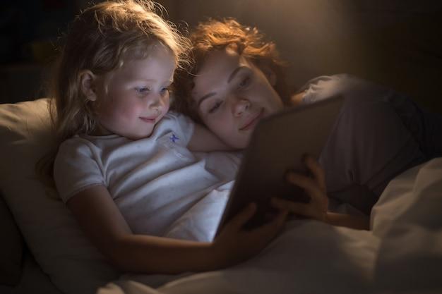 Jolie fille lisant un livre électronique avec sa mère