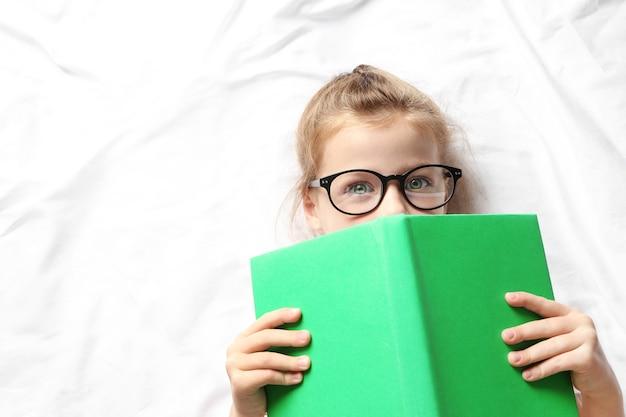 Jolie fille avec livre couché sur des draps blancs