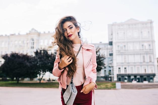 Jolie fille avec une longue coiffure en pantalon vineux pose en ville.