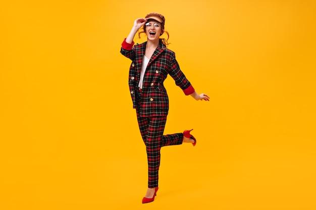 Jolie fille à lunettes, casquette et costume saute sur le mur orange
