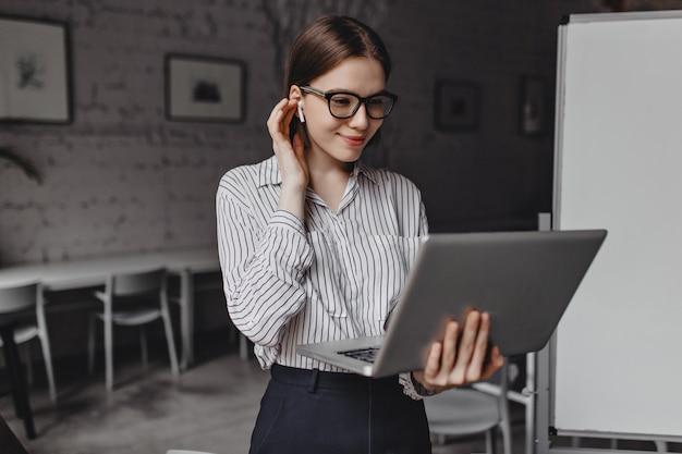 Jolie fille à lunettes élégantes sourit, met des écouteurs sans fil et tient un ordinateur portable ouvert sur fond de bureau.