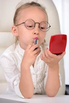 Jolie fille avec des lunettes en regardant dans le miroir et le maquillage