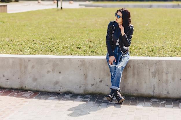 Jolie fille à lunettes de soleil sur l'herbe dans le parc