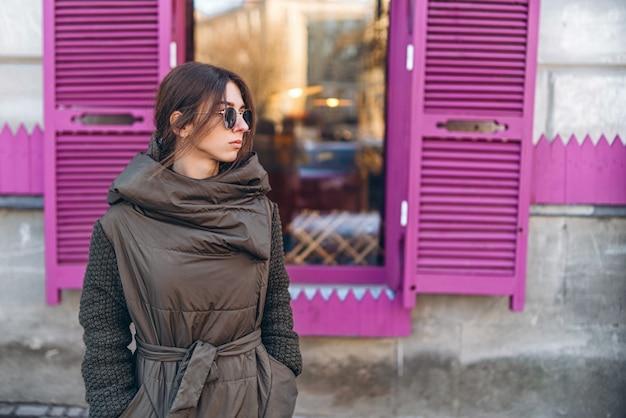 Jolie fille à lunettes de soleil manteau marchant en plein air.